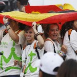 People shelter themselves from the rain under Spanish flags as they wait for the arrival of Pope Benedict XVI in Madrid